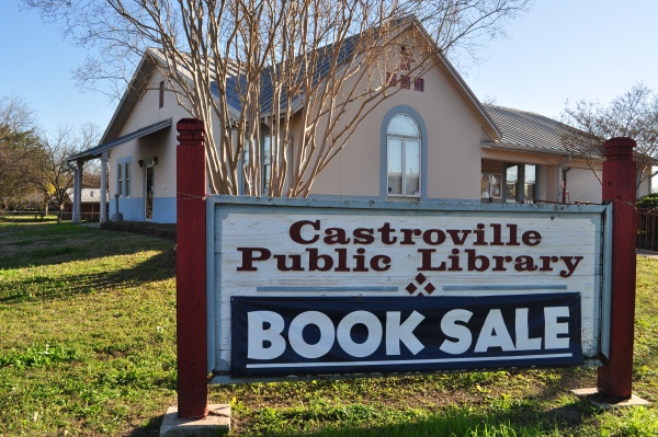 Castroville Public Library sign with a banner saying Book Sale
